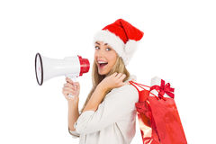 Festive blonde holding megaphone and bags Stock Image