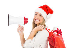 Festive blonde holding megaphone and bags Royalty Free Stock Photo
