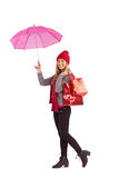 Festive blonde holding umbrella and bags Stock Photo