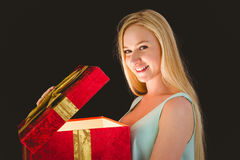 Festive blonde opening a gift Royalty Free Stock Image