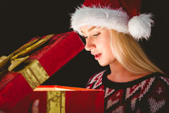 Festive blonde opening a gift Royalty Free Stock Images