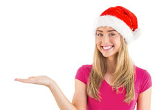 Festive blonde presenting with hand Stock Photography