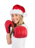 Festive blonde punching with boxing gloves Stock Images