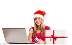 Festive blonde shopping online with laptop Royalty Free Stock Photography