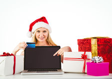 Festive blonde shopping online with laptop Stock Photography