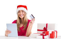 Festive blonde shopping online with tablet Stock Image