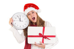 Festive blonde showing a clock and gift Royalty Free Stock Photo