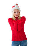 Festive blonde smiling at camera and blowing over hands Stock Photo