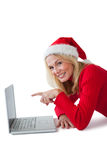 Festive blonde smiling at camera and pointing to laptop Stock Images