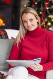 Festive blonde woman using her credit card and tablet pc Royalty Free Stock Images