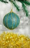 Festive blue decoration toy ball with a pattern. On a New Year tree on a beautiful bokeh background with a gold garland Royalty Free Stock Photography