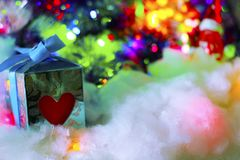 Cute gift box with red heart and blue ribbon on snowy  backgrou Stock Photo