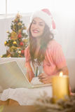 Festive brown hair shopping online with laptop at christmas Royalty Free Stock Photography