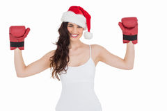 Festive brunette in boxing gloves with arms raised Royalty Free Stock Photography