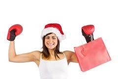 Festive brunette in boxing gloves holding shopping bags Stock Photography