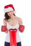Festive brunette in boxing gloves opening shopping bag Royalty Free Stock Photography