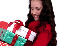 Festive brunette carrying pile of gifts stock footage
