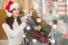 Festive brunette decorating a christmas tree Royalty Free Stock Photos