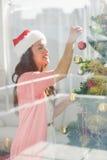 Festive brunette decorating a christmas tree Royalty Free Stock Photo