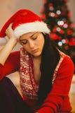 Festive brunette feeling sad at christmas Royalty Free Stock Image