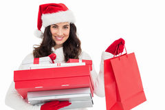 Festive brunette holding christmas gifts and shopping bags Royalty Free Stock Image
