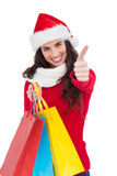 Festive brunette holding gifts and thumb up Royalty Free Stock Images
