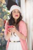 Festive brunette holding mug and thinking Stock Photos