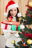 Festive brunette holding pile of gifts near a christmas tree Royalty Free Stock Photos
