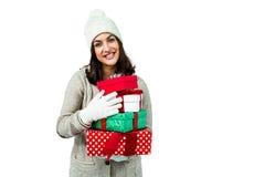 Festive brunette holding pile of gifts Stock Photo