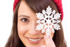 Festive brunette holding snowflake decoration Stock Photos