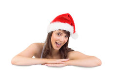 Festive brunette leaning on large poster Royalty Free Stock Photography