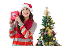Festive brunette listening gift by the christmas tree Royalty Free Stock Image