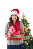 Festive brunette opening gift by the tree Royalty Free Stock Image