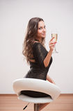Festive brunette. Portrait of festive young brunette holding glass of champagne Royalty Free Stock Photography