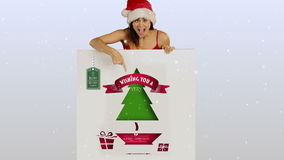 Festive brunette presenting a christmas card stock footage