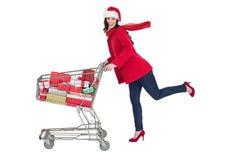 Festive brunette pushing trolley full of gifts Stock Image