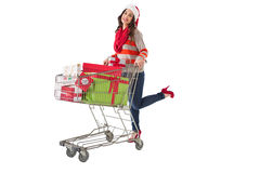 Festive brunette pushing trolley full of gifts Royalty Free Stock Photography