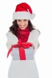 Festive brunette in santa hat giving gift Stock Images