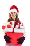 Festive brunette with santa hat holding many gifts Royalty Free Stock Photography