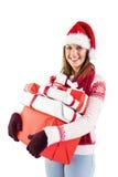 Festive brunette with santa hat holding many gifts Stock Photo