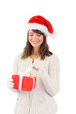 Festive brunette in santa hat opening a gift Stock Photos