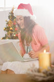 Festive brunette shopping online with laptop at christmas Stock Image