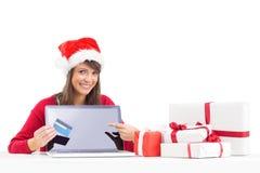 Festive brunette showing a laptop Royalty Free Stock Image