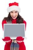 Festive brunette showing a laptop Royalty Free Stock Photo