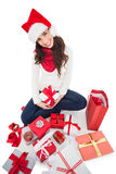 Festive brunette sitting and wrapping christmas presents Royalty Free Stock Image