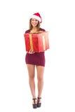 Festive brunette smiling at camera offering gift Stock Images