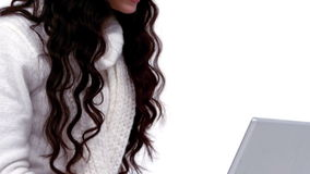 Festive brunette using her laptop. On white background in slow motion stock video