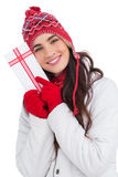 Festive brunette in winter clothes pointing gift Stock Photo