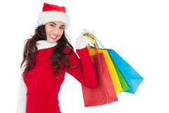 Festive brunette in winter wear holding shopping bags Stock Photography