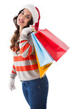 Festive brunette in winter wear holding shopping bags Royalty Free Stock Image